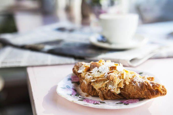 Um croissant com cobertura de amêndoas está em cima de um pequeno prato, com florezinhas. Em cima da mesma mesa, mas ao fundo da foto, uma xícara situa-se em cima de vários jornais