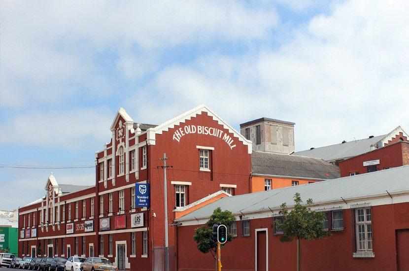 """O grande prédio e a frente do restaurante. Na lateral, há, em letras garrafais, o seu nome """"The Old Biscuit Mill"""""""