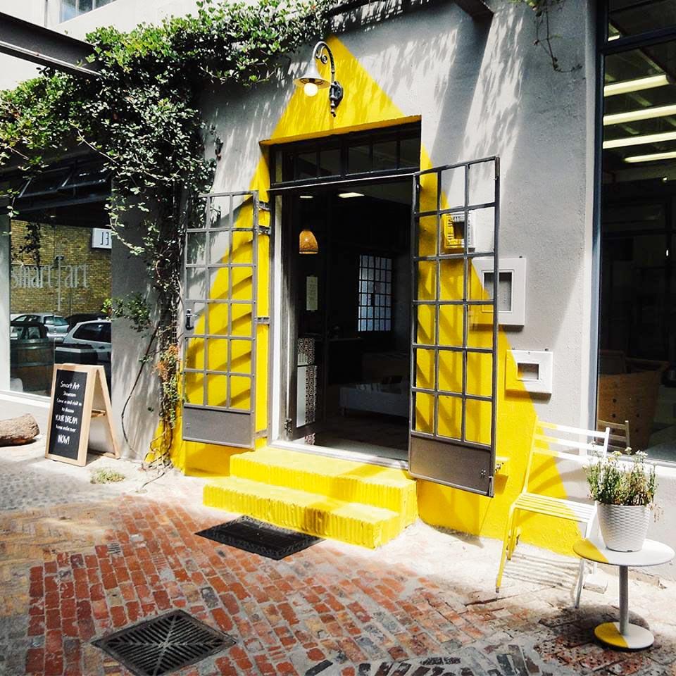 Entrada arrojada e moderna, com plantas e o desenho de um triângulo gigante que ocupa toda a porta