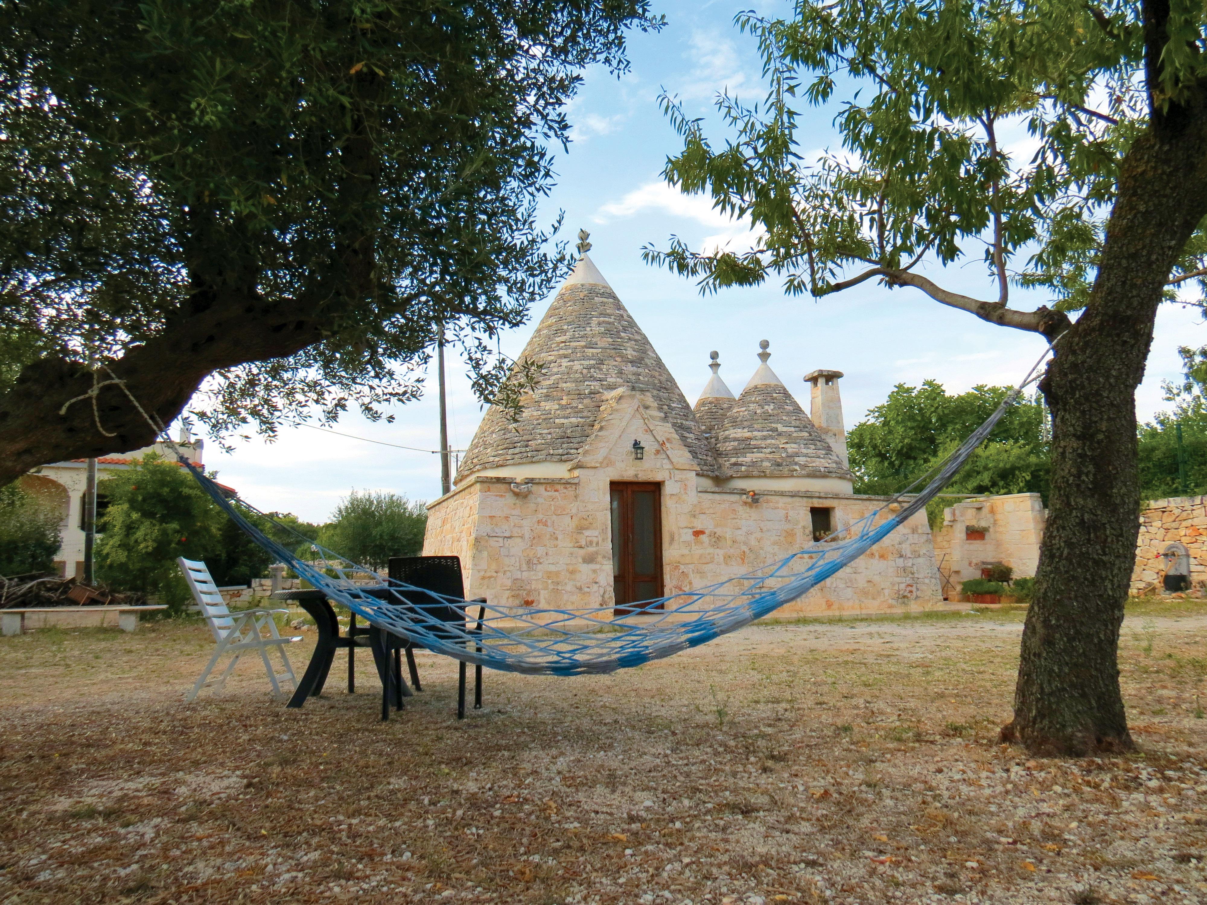 Casa em estilo trullo, com um quintal na frente, no qual duas árvores suportam uma rede