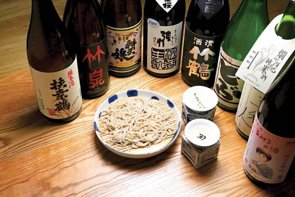 8 garrafas de saquê reunidas em um semicírculo, com uma tigela de macarrão no centro