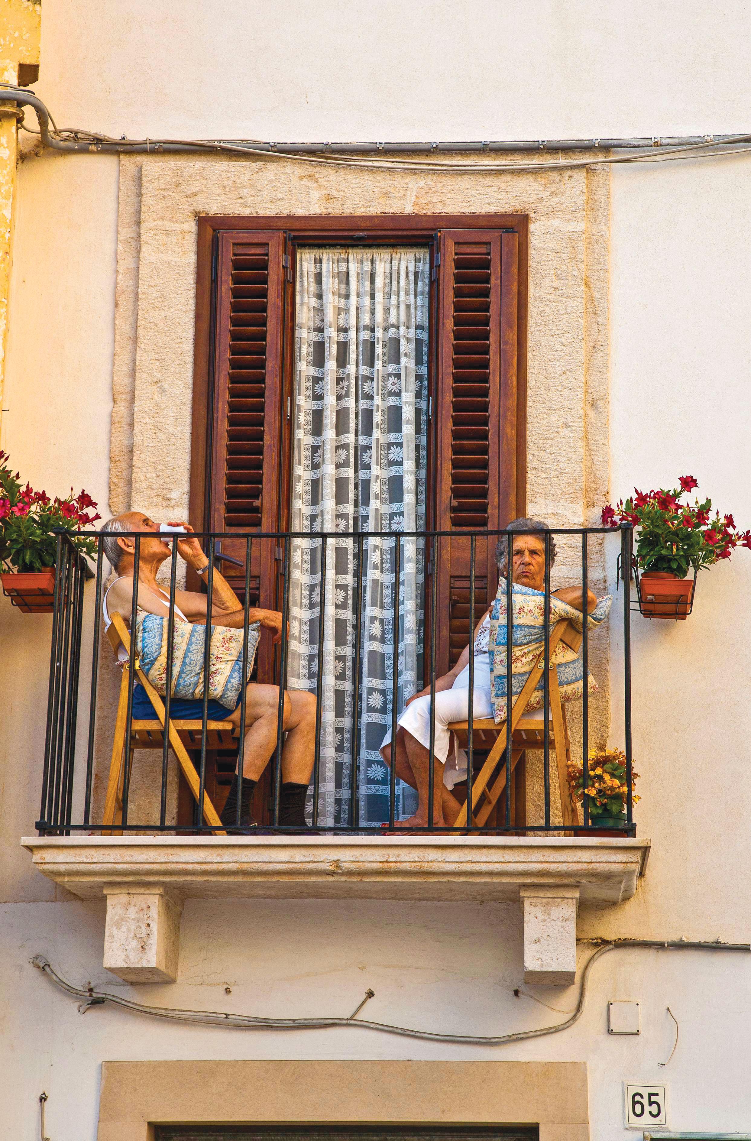 Uma senhora e um senhor descansam de forma descontraída na varada de sua casa, a qual é decorada com vasos de flores