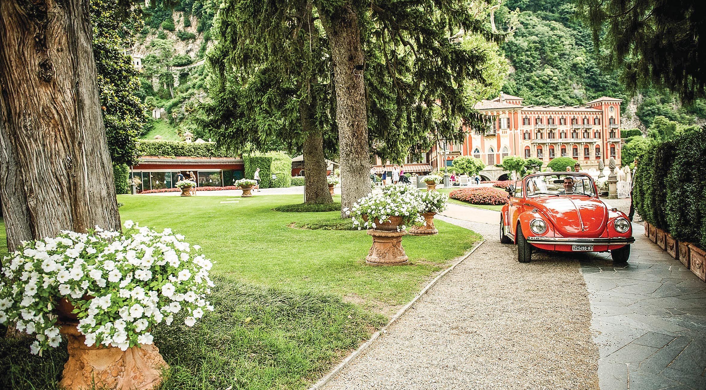 Um fusca conversível percorre o caminho de saída do suntuoso jardim do hotel Villa d'Este, que se encontra ao fundo
