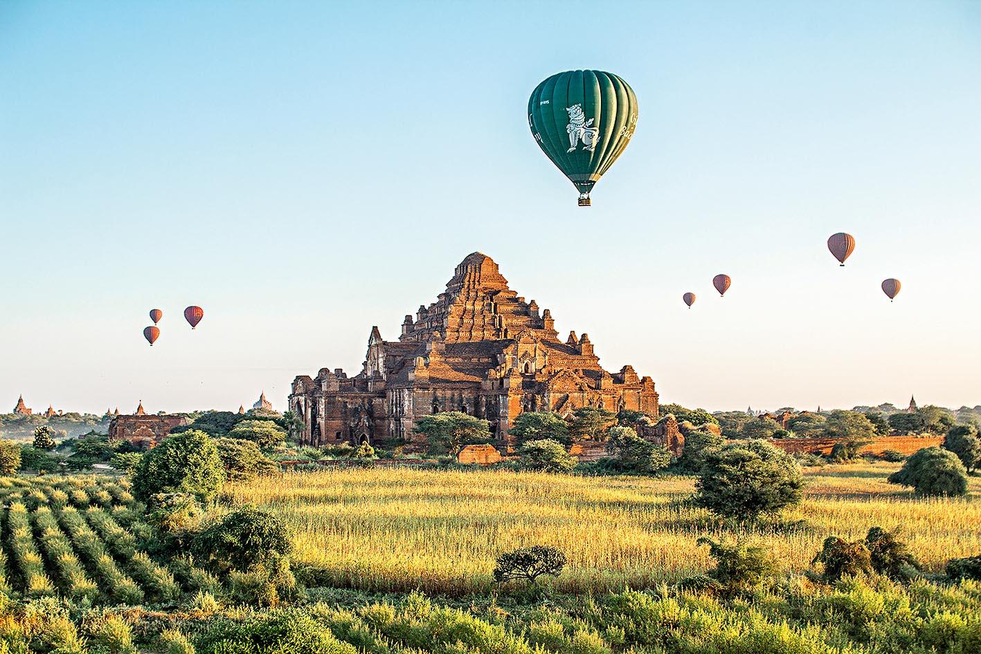 Balões coloridos sobrevoam as estupas e o gramado da região. Ao fundo, outros templos aparecem ao longo do horizonte