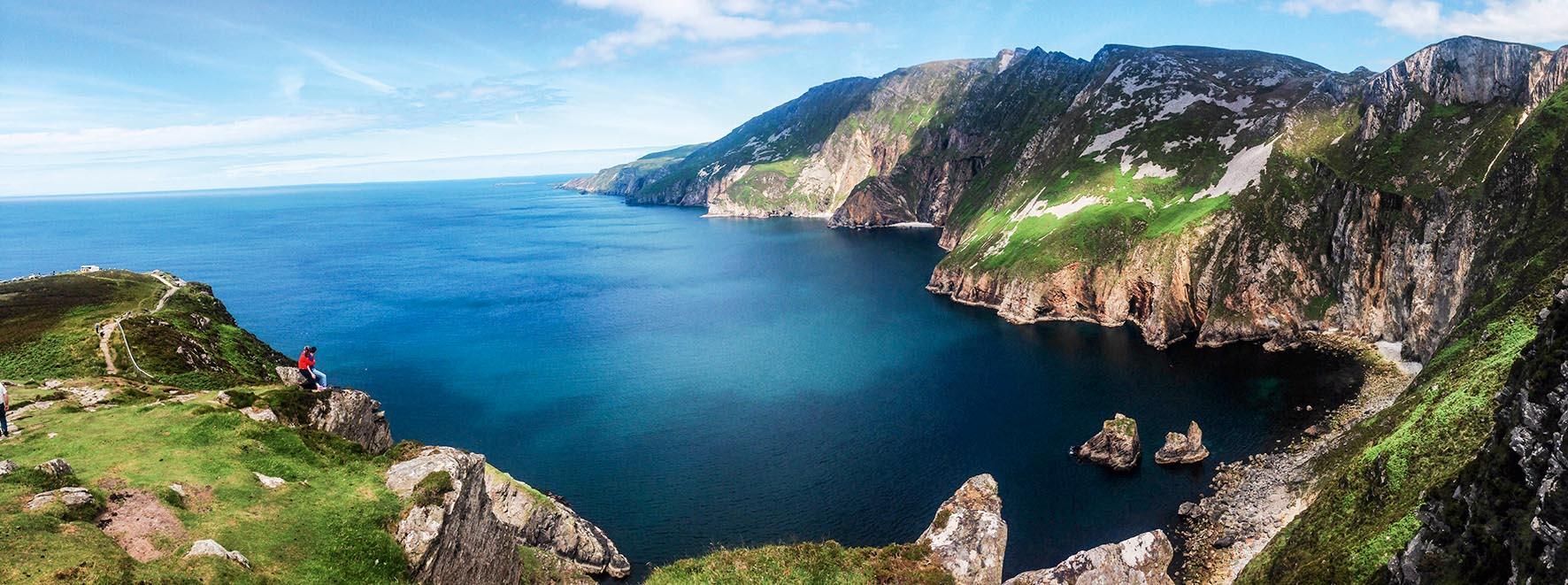 Em primeiro plano, montanhas à beira d'água formam uma baía natural. Ao fundo, o horizonte marítimo