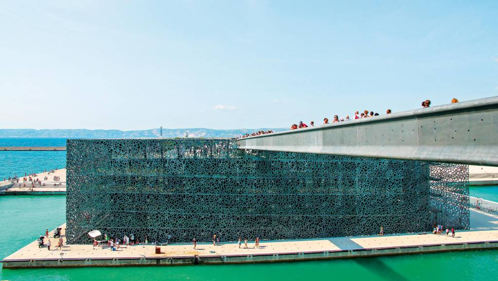 Imagem lateral da ponte acima do mar em direção ao museu de Marselha, no centro da foto.