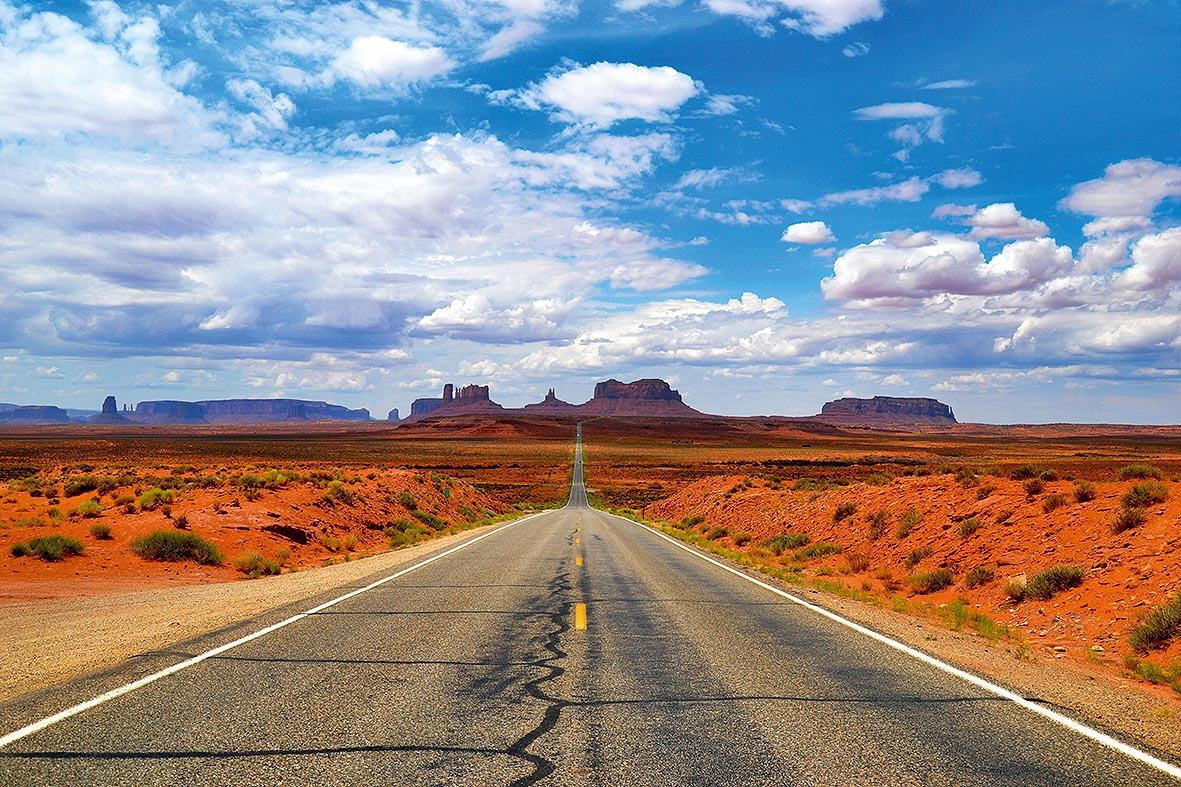 Uma estrada vazia corre para o horizonte, onde há vários cânions. Ao lado, paisagem desértica típica dos Estados Unidos.