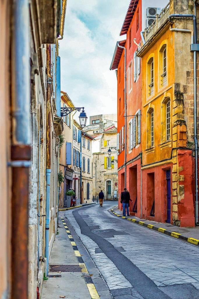 Foto de uma rua de Arles, estreita e cercada por casas de três a quatro andares