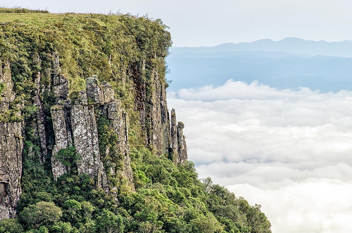Um precipício com várias plantas e árvores ao longo do lado da montanha. Ao fundo, várias nuvens e, no horizonte, uma cadeira de montanhas. A foto é vista, provavelmente, de outro ponto da Serra do Rio do Rastro.