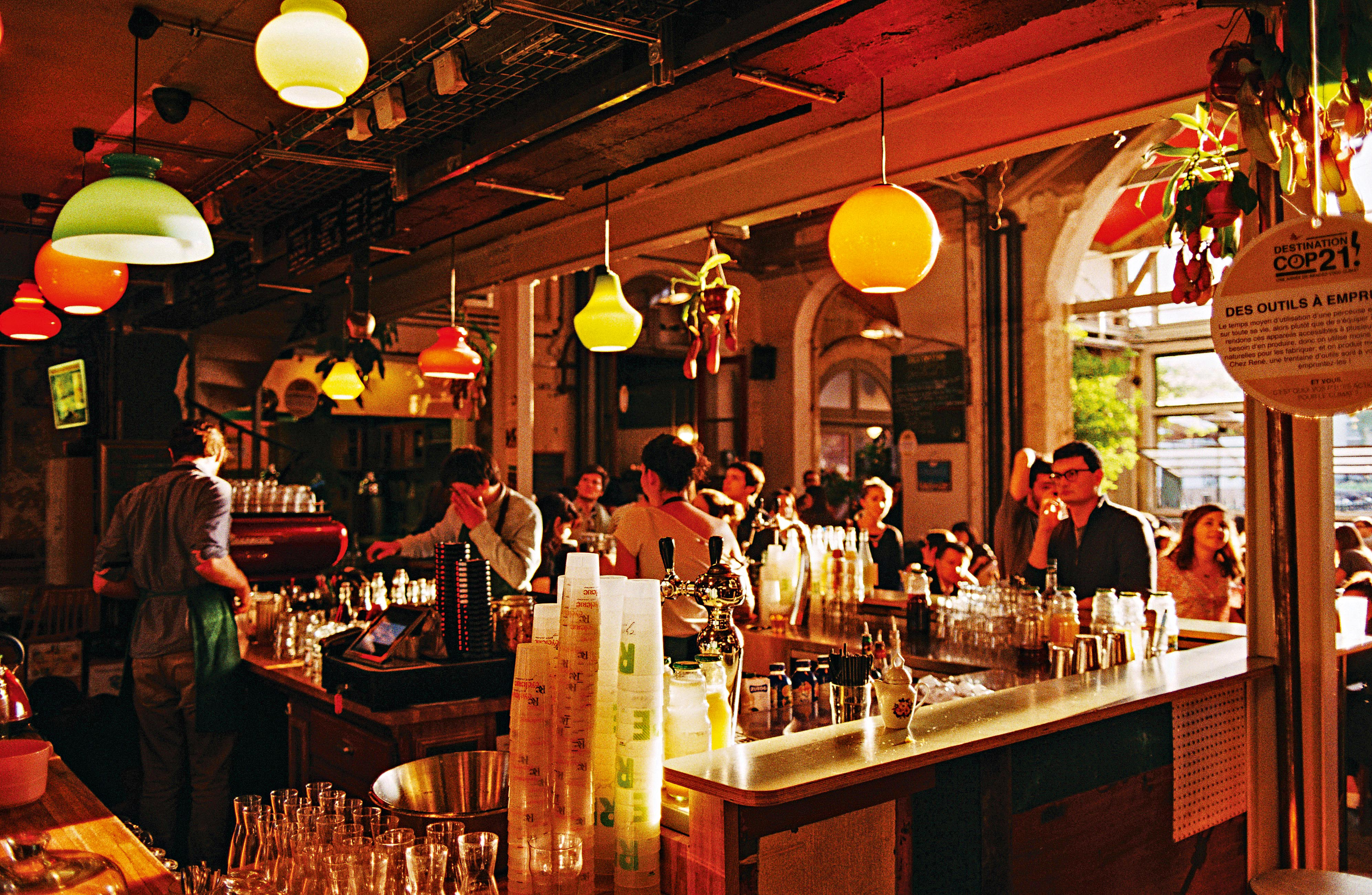 Um bar cheio de clientes, visto da parte lateral do balcão e de frente para a porta, por onde entra a luz do sol.