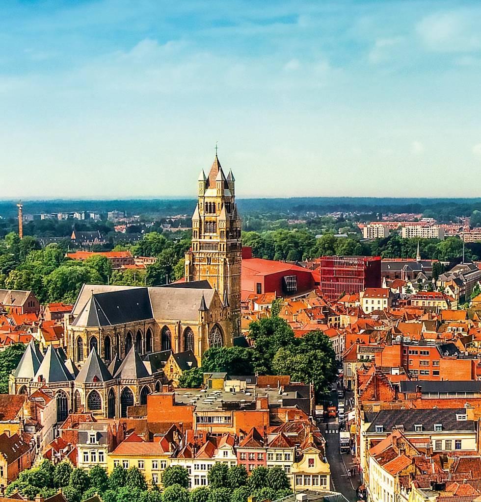 A torre da catedral se eleva acima dos outros prédios e casas em meio às ruas de Bruges