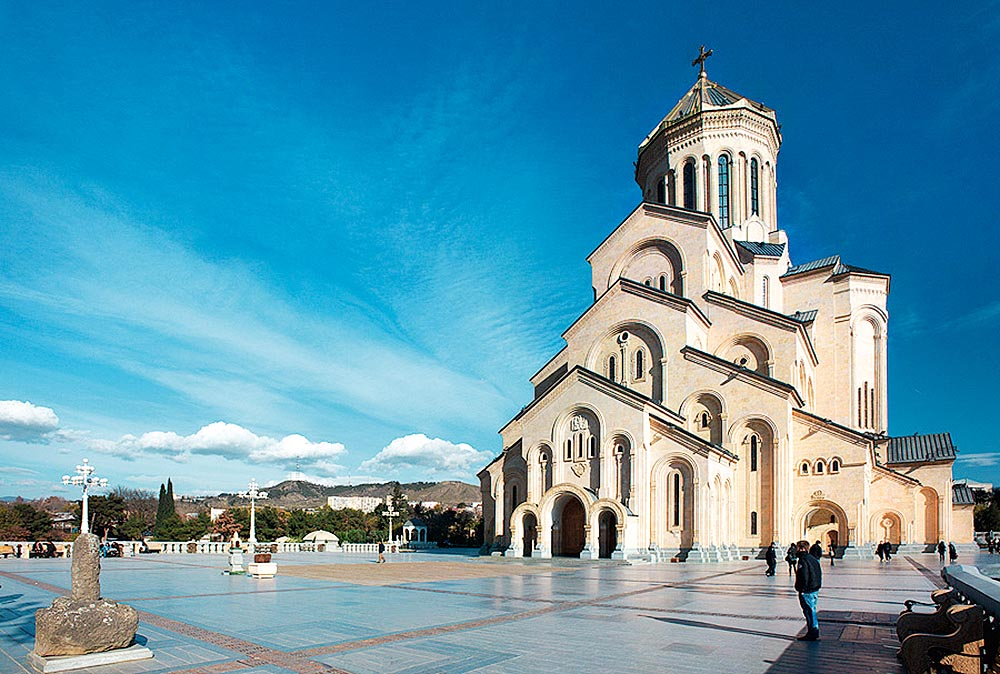 Uma grande catedral, com uma arquitetura que divide a sua altura em camadas, localizada em uma grande praça com montanhas ao fundo