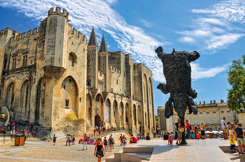 Um palácio medieval imponente se ergue no canto esquerdo da foto, cercado por turistas. À direita, uma escultura imita um elefante se equilibrando perfeitamente pela tromba