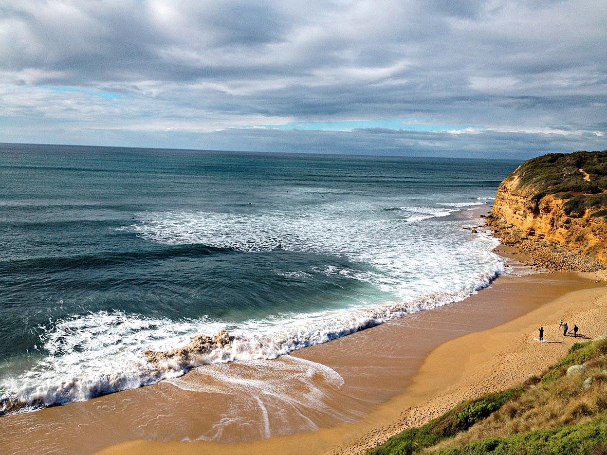 Ondas quebram em uma praia, enquanto surfistas preparam pranchas de surfe. O local é emoldurado por uma elevação, de onde a foto é tirada. Ou seja, toda a cena é vista do alto.