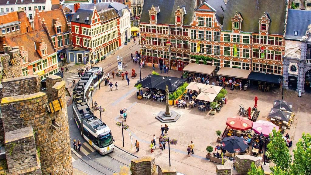 Uma praça central, por onde passa o trilho de um bonde elétrico e moderno