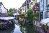 Visão do curso de um rio, com casas de estilo típico francês em uma margem e um restaurante na outra