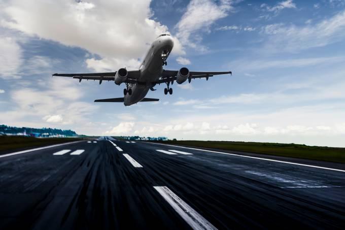 Avião pousando no fim da tarde em pista de aeroporto