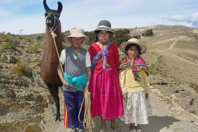 Crianças indígenas bolivianas e lhama na Isla del Sol, no Lago Titicaca, na Bolívia