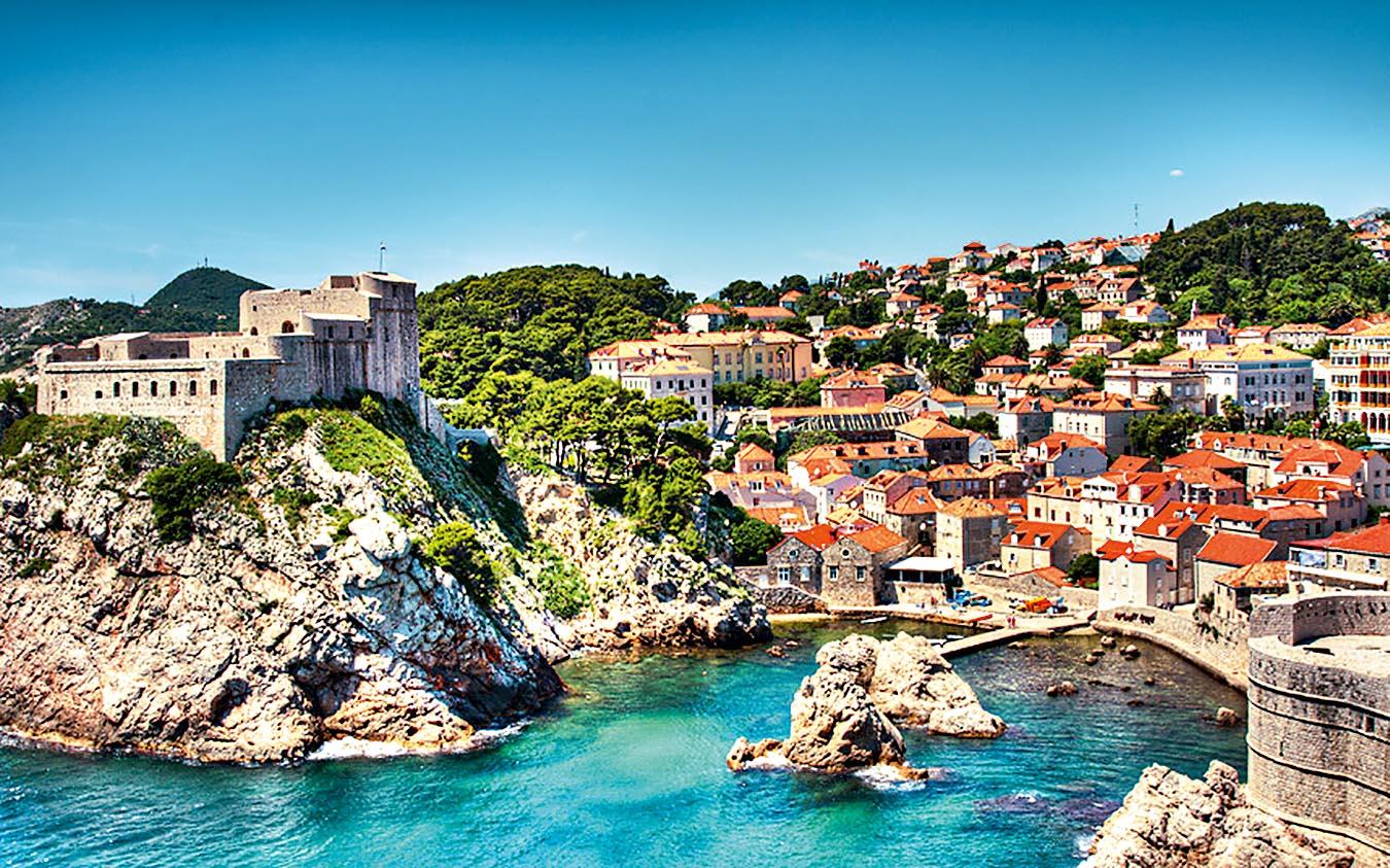 Várias casinhas e um forte preenchem a paisagem íngreme que cerca o porto de Dubrovnik