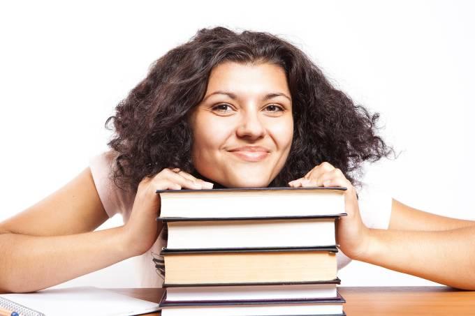 Estudante mulher sorri em cima de pilha de livros