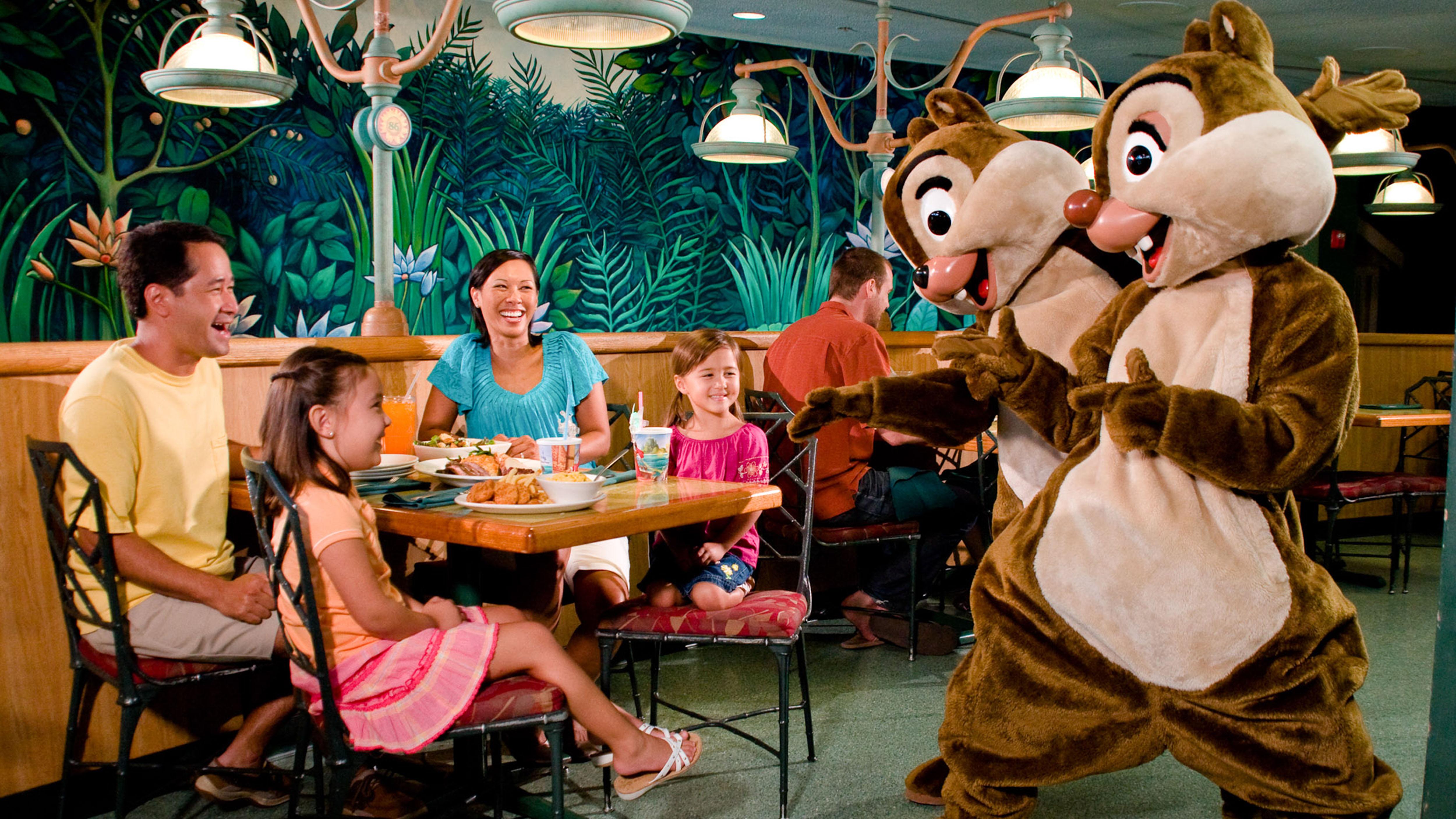 Crianças sentadas na mesa do restaurante estão cercada por seus pais e os personagens Tico e Teco