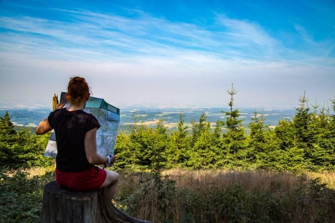 Mulher turista lê mapa de cidade com cenário de árvores ao fundo, no horizonte