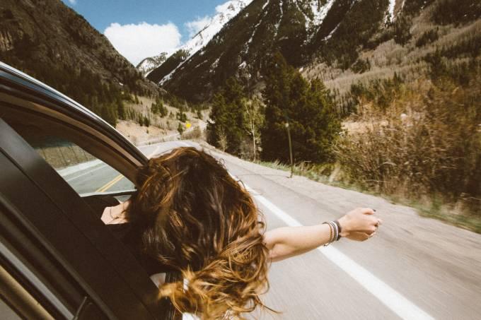 Mulher em carro na rodovia com picos nevados ao fundo