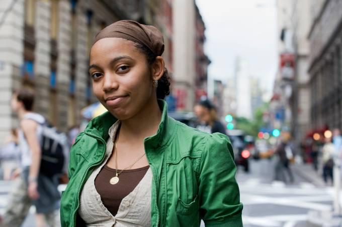 Mulher negra viajante olhando para a câmera em rua de cidade à luz do dia