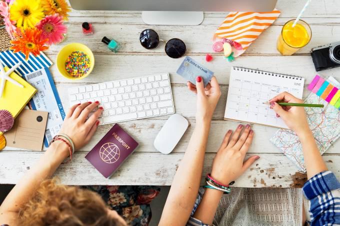 Mulheres planejam viagem em cima de mesa com computador, passaporte e cartão de crédito