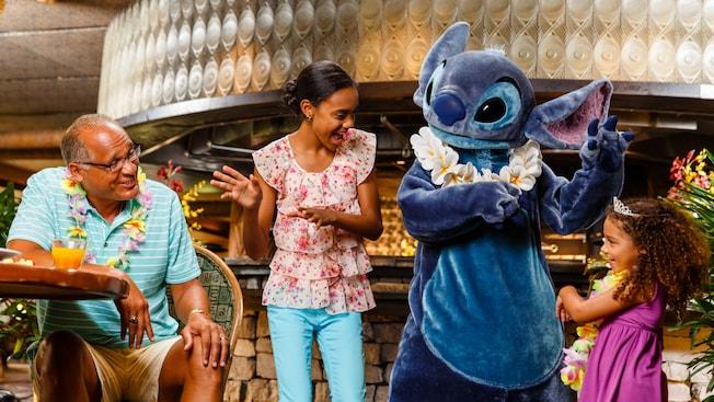 Ao lado do pai, duas meninas, uma mais velha e outra mais nova, brincam de dançar a hula junto com o personagem Stitch