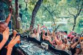 DJ organiza festa à beira de um rio, apinhando pessoas em frente à mesa com acessórios extravagantes