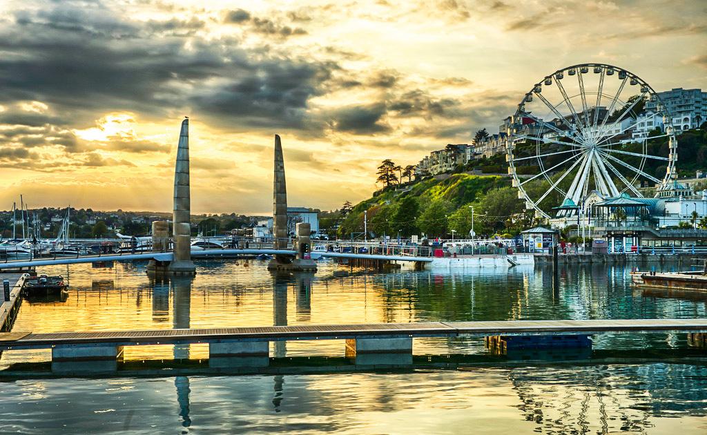 Imagem de uma cidade litorânea, com uma roda gigante no cais e barcos aportados. As casas ficam sobre uma colina no lado direito