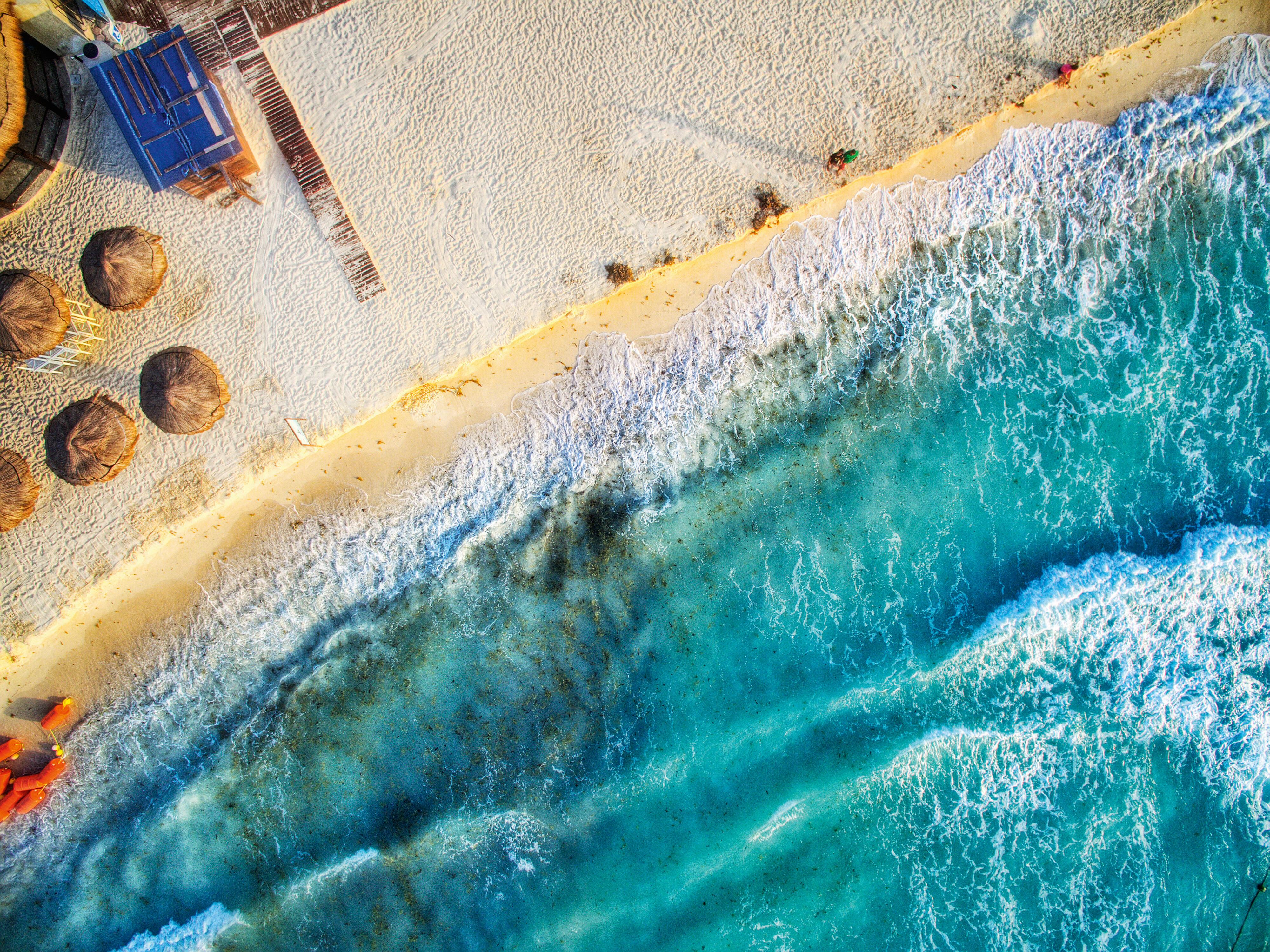 Vista aérea do praia, com metade da foto encoberta por ondas suaves do mar azul