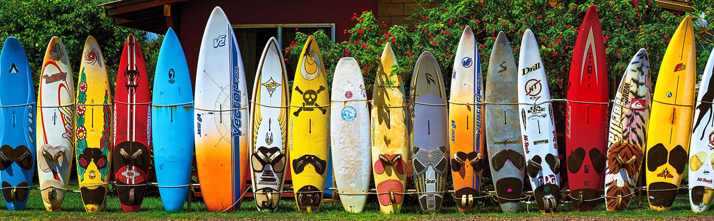 pranchas de surfe de vários tamanhos enfileiradas de pé, unidas por uma corda que envolve toda a fila