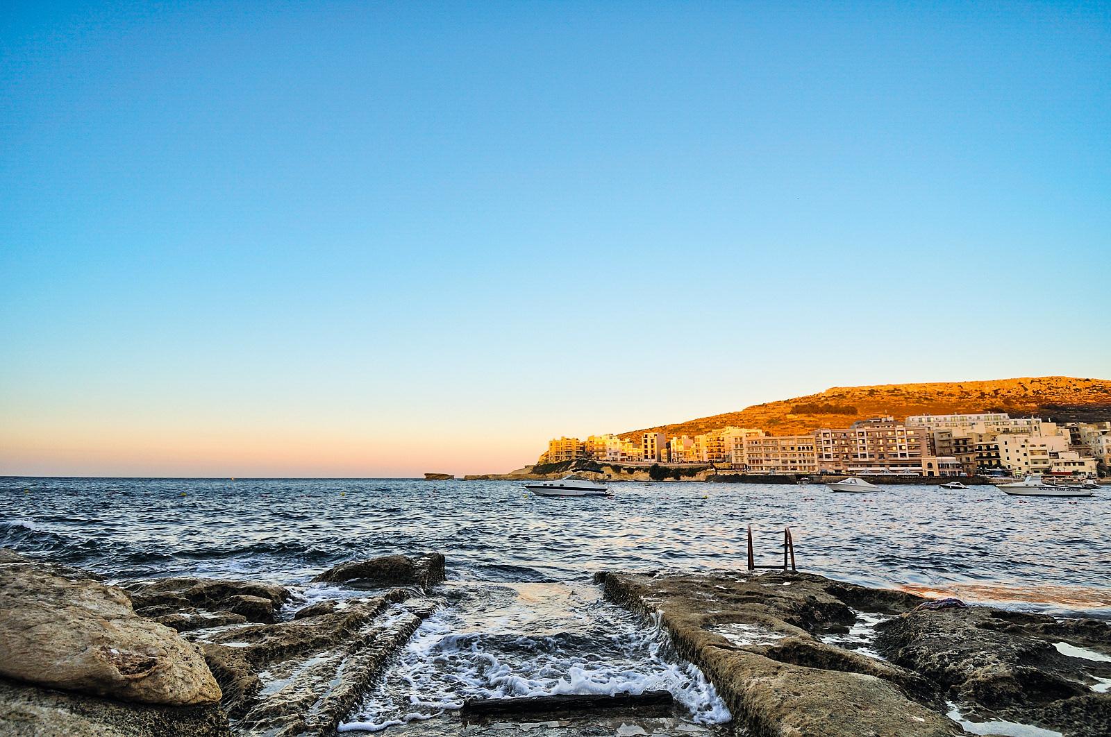 Vista para o mar sem praia, com uma cidade à distância