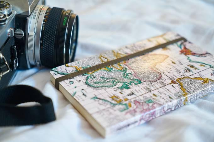 Diário de viagem e câmera fotográfica em cima de mapa