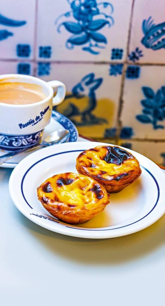 Dois pastéis de Belém em ambiente típico português, com prataria e azulejo simples