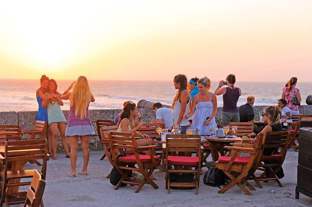 Grupo de jovens aproveitam o clima quenta em café no topo de uma muralha fortificada em frente à praia