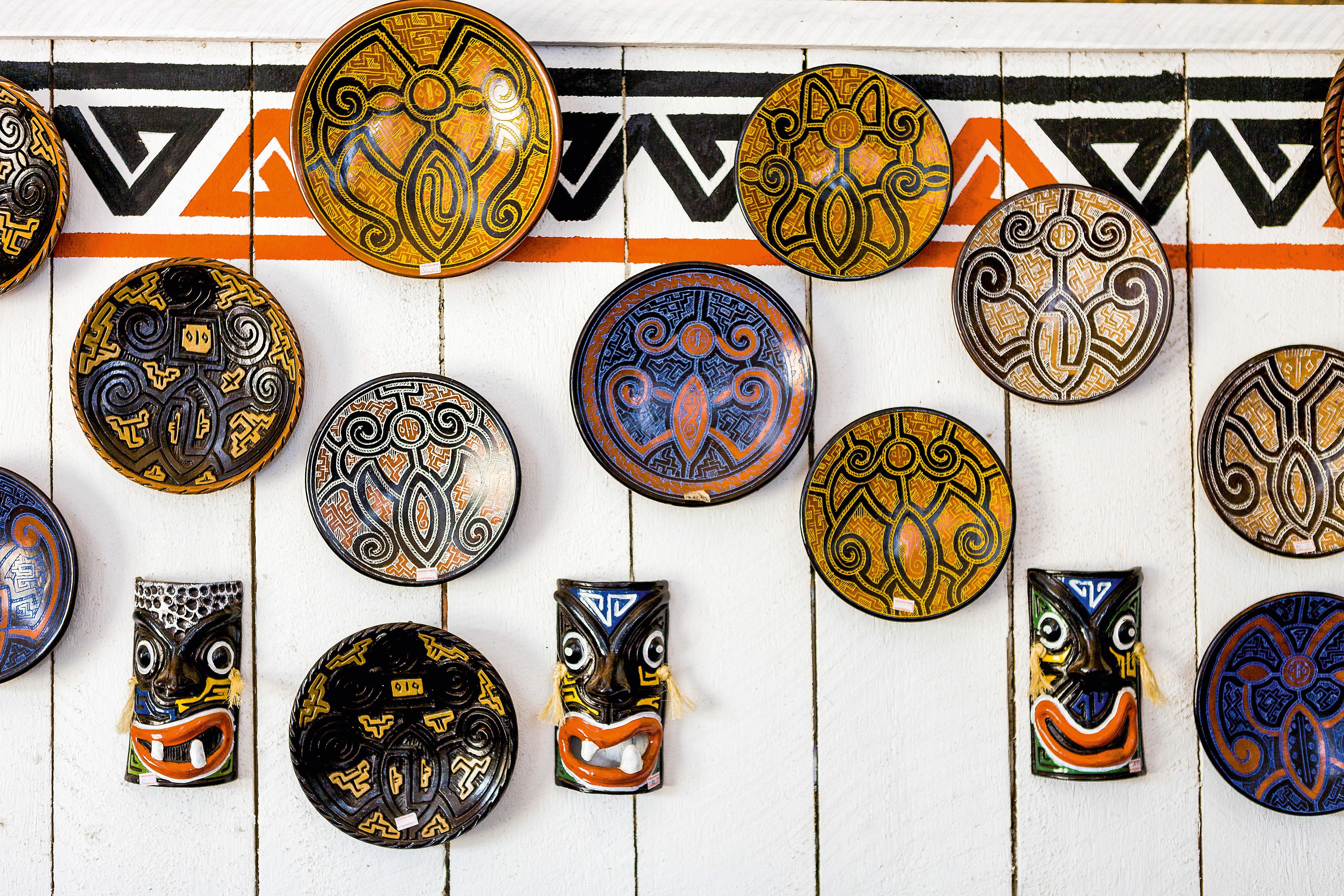 Pratos e máscaras artesanais com desenhos diferentes e tribais penduradas em uma parede