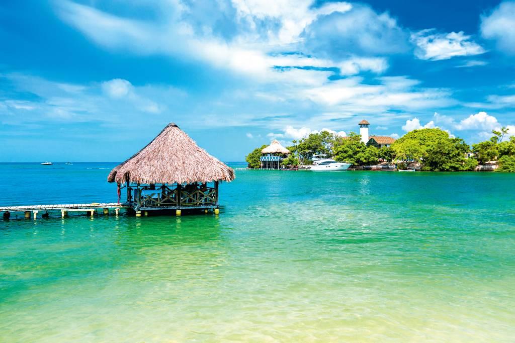 Cabanas em cima do mar claro e abaixo de um céu limpo e ensolarado