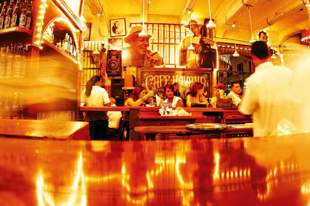 Interior de um café movimentado, com fotomontagens de personagens importantes para a salsa nas paredes