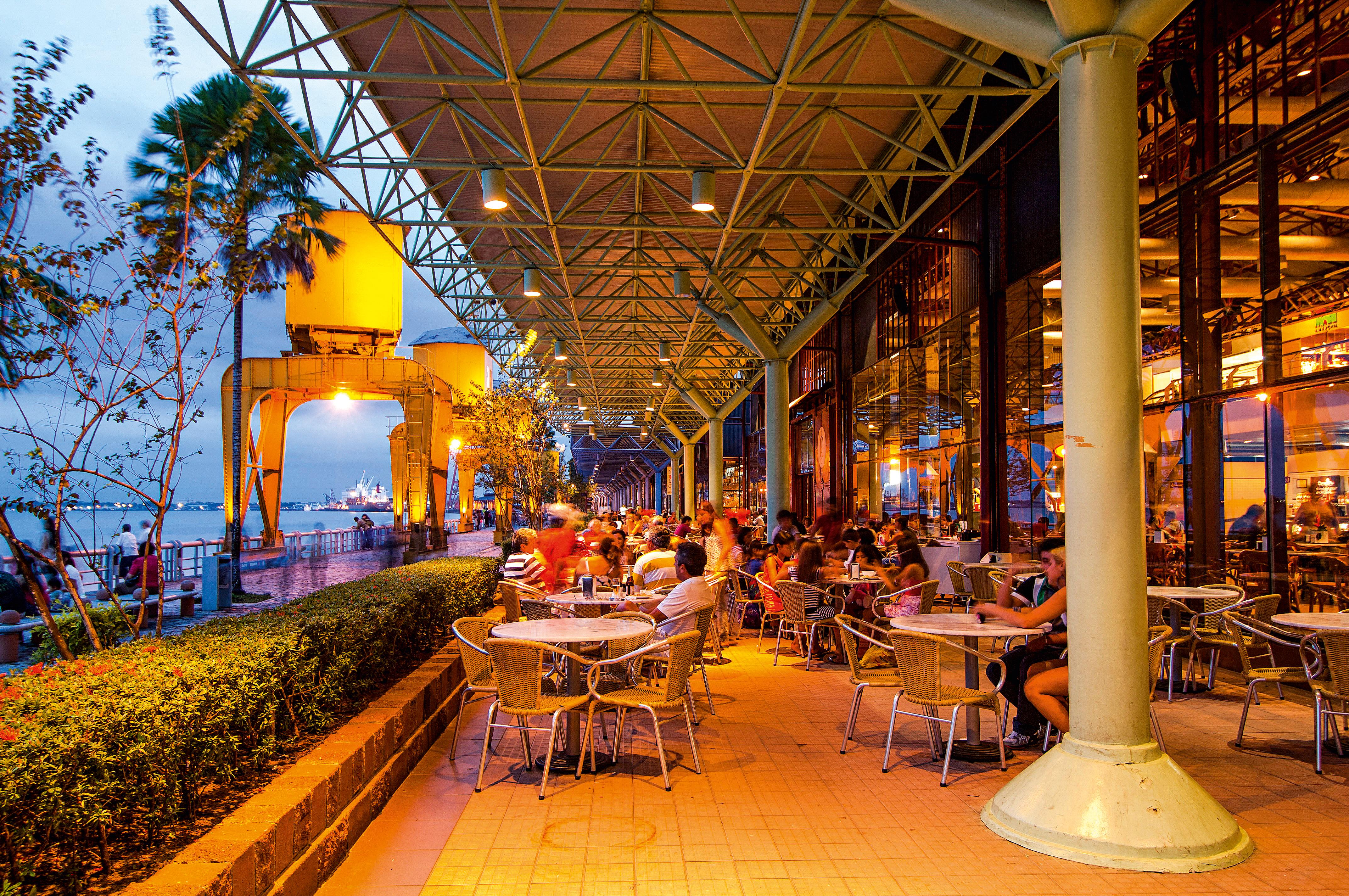 Uma passarela ao lado do mar cheia de mesinhas e lojas se estende sob o crepúsculo