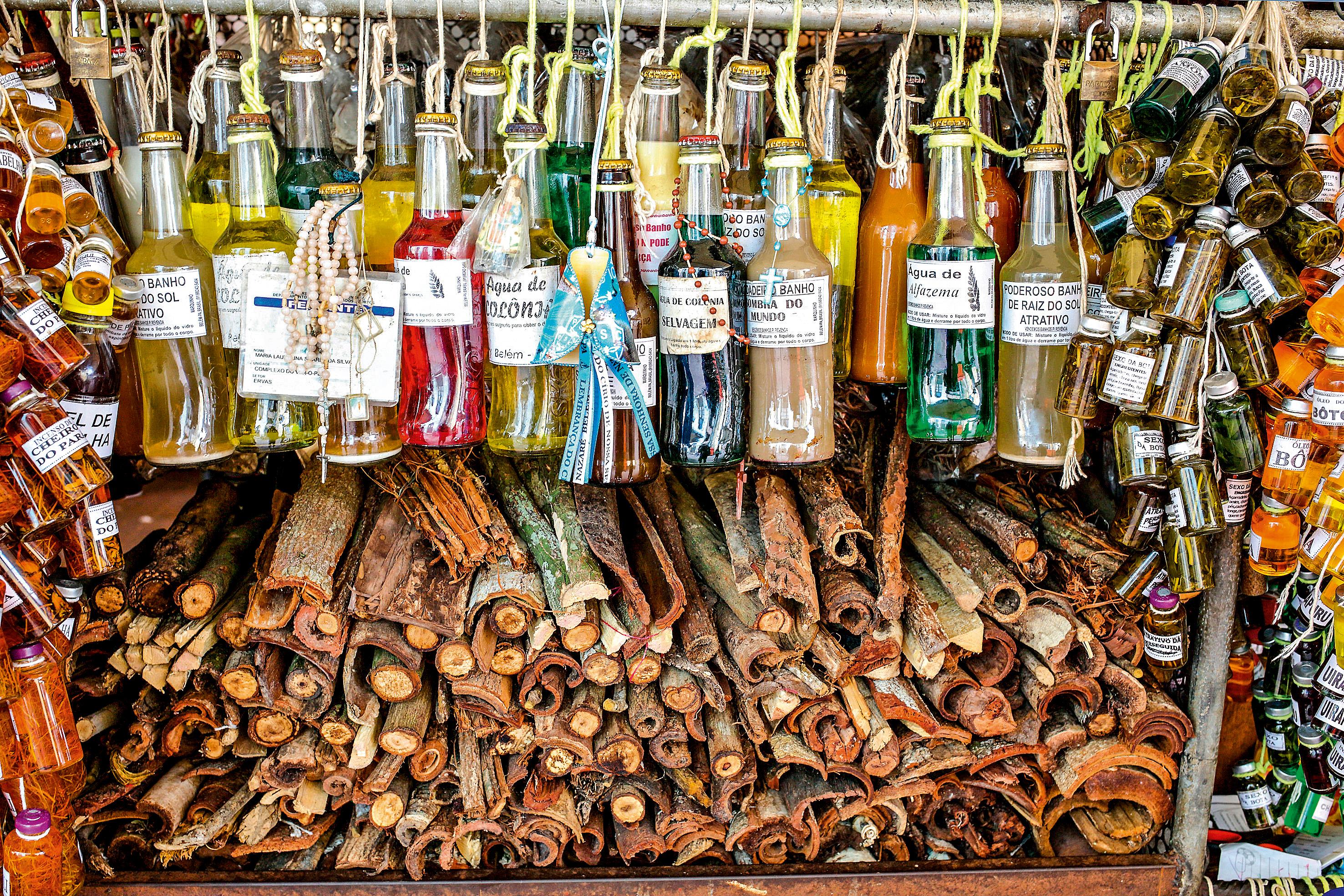 Garrafas de vidro penduradas por cordas amarradas ao pescoço vendem diversos tipos de líquidos. dos lados, garrafinhas também estão à venda, penduradas ao longo estande, e embaixo há uma pilha de cascas de árvore