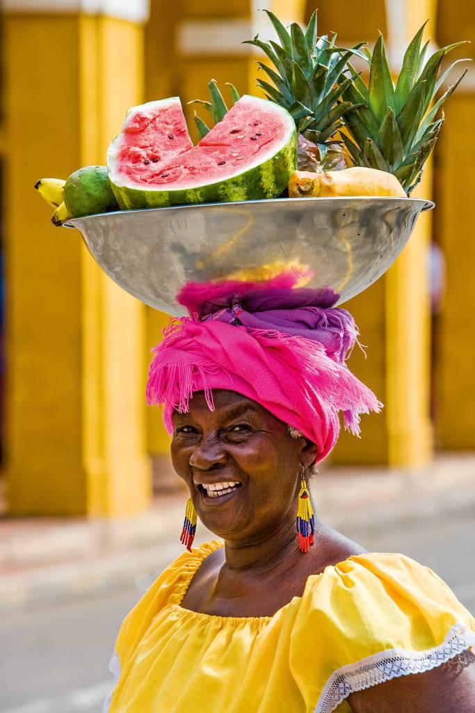 Mulher em trajes de cores fortes carregando uma bacia de frutas em cima da cabeça. É possível distinguir meia melancia, três abacaxis, um abacate, bananas e mais uma fruta.