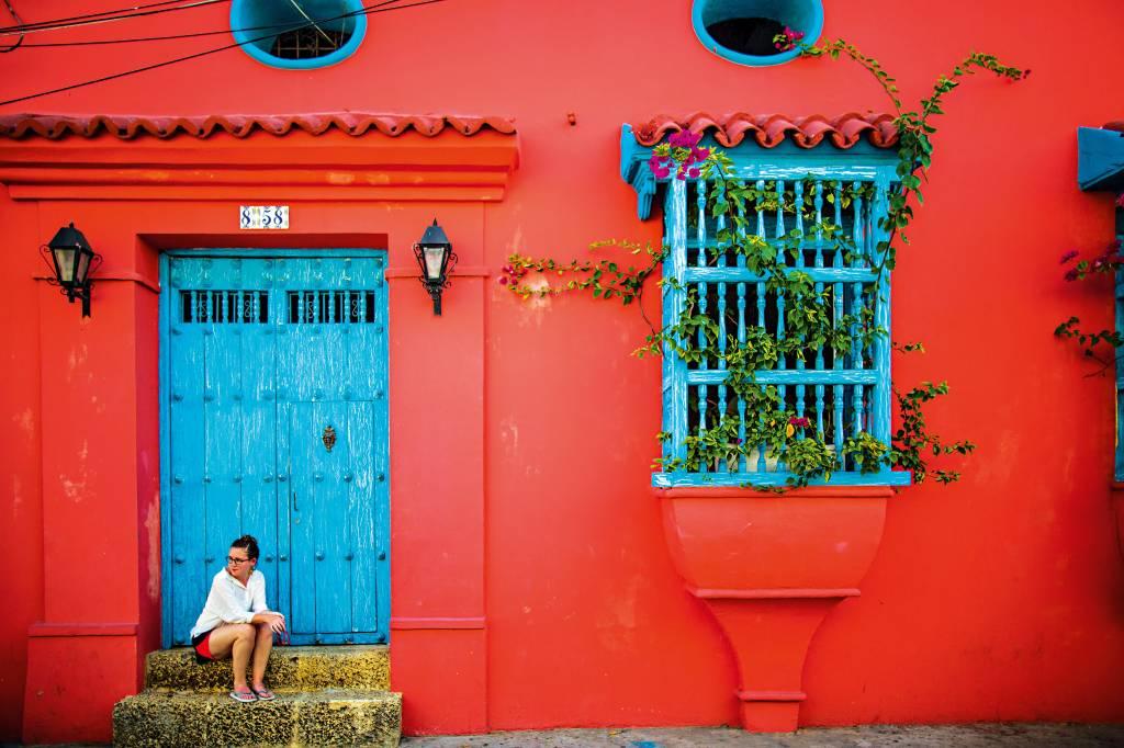 Mulher senta-se na fachada de uma casa típica colombiana, à direita da foto. À esquerda, uma trepadeira surge de dentro da janela