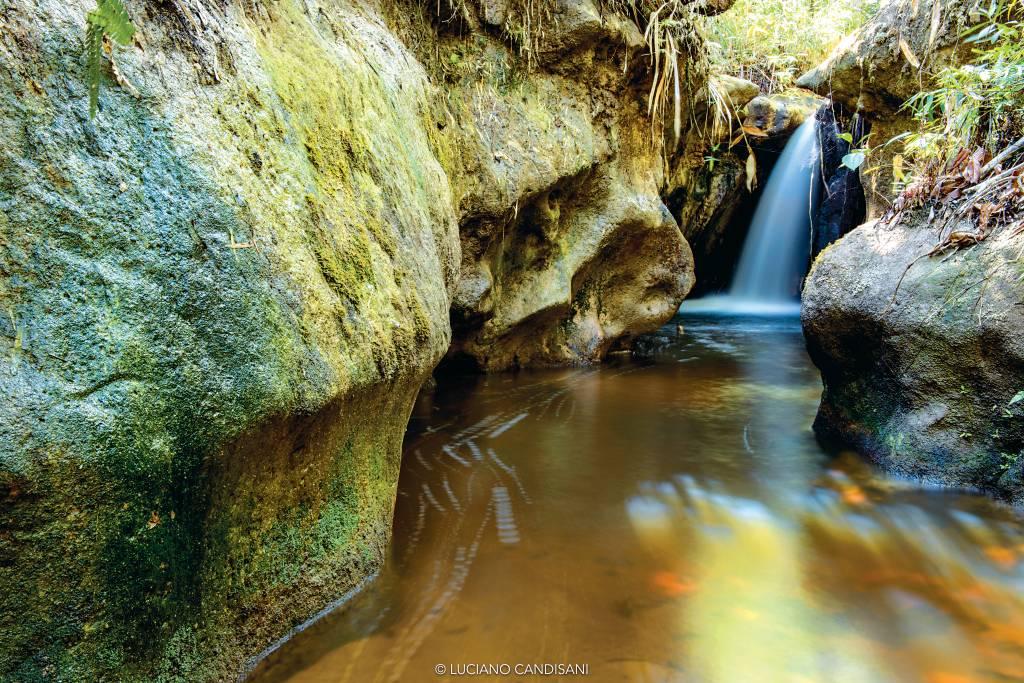 Curso de rio ladeado por pedras altas, com uma pequena cachoeira ao fundo
