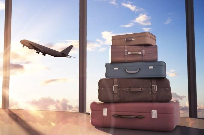 Malas de viagem com avião decolando ao fundo