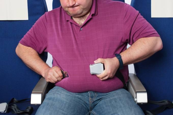 Passageiro obeso tenta apertar o cinto de segurança em poltrona de avião comercial