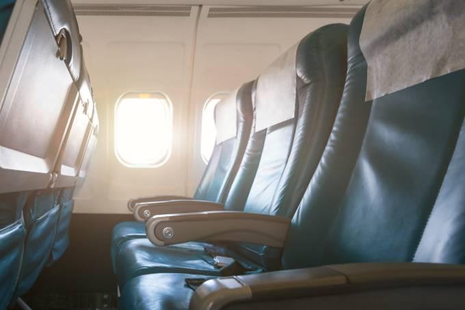 Poltronas de cabine de avião comercial com janelas ensolaradas