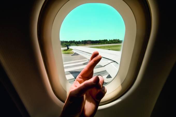 Pessoa cruzando os dedos em frente a janela de um avião prestes a decolar